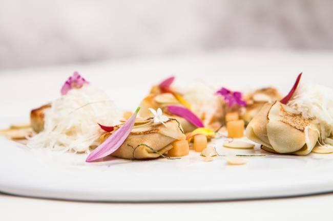 Falso tortelli de pupunha da chef Helena Rizzo sobre prato plano de louça branca.