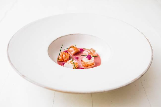 Prato fundo de louça branca com sopa de jabuticaba e pedaços de lagostim.