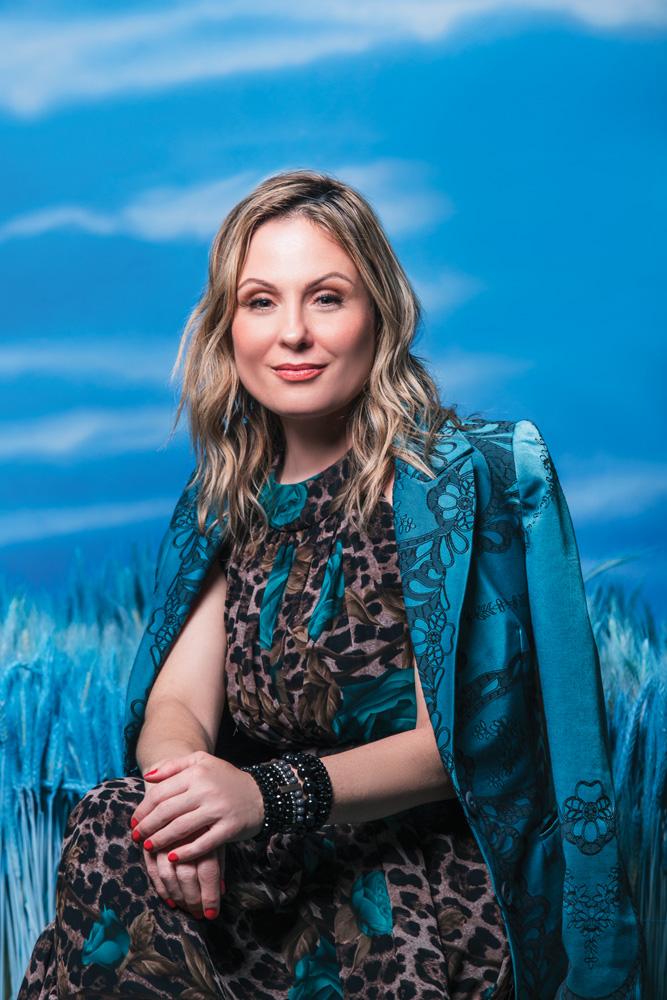 Ellen Sharkany posando para a foto usando blusa de oncinha, com as mãos juntas, e com uma blusa de mão comprida em seus ombros. o fundo é azul