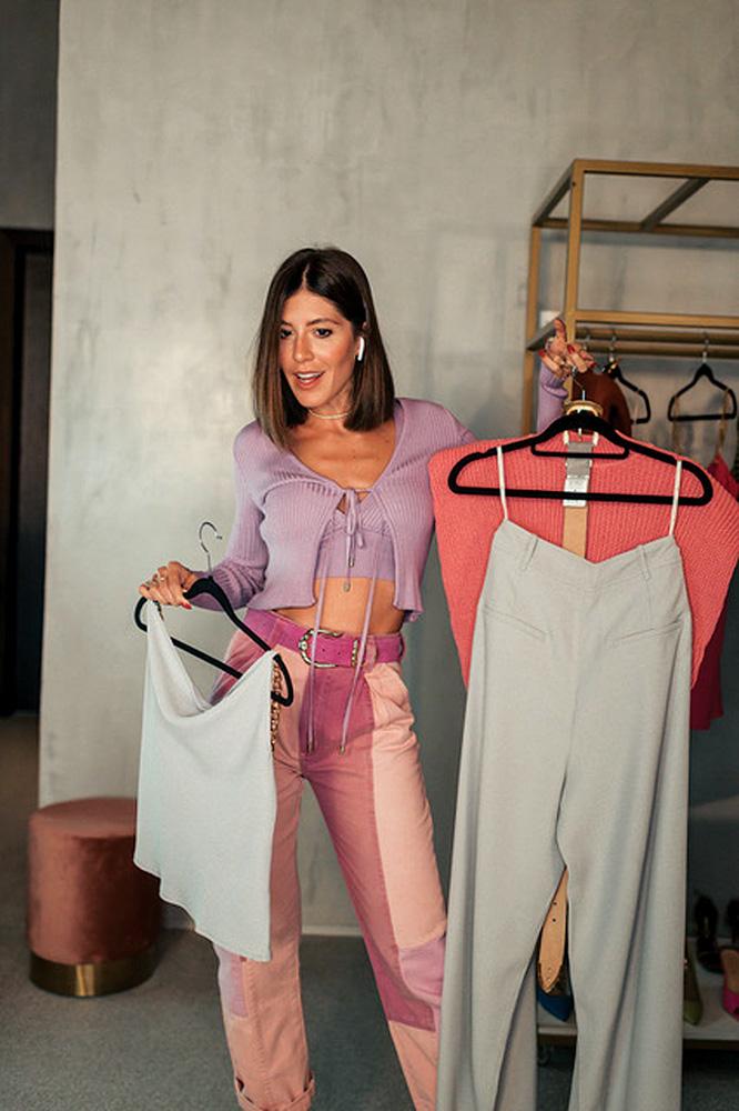 influenciadora Isa Domingues olhando para um ponto fixo enquanto segura cabides com roupas