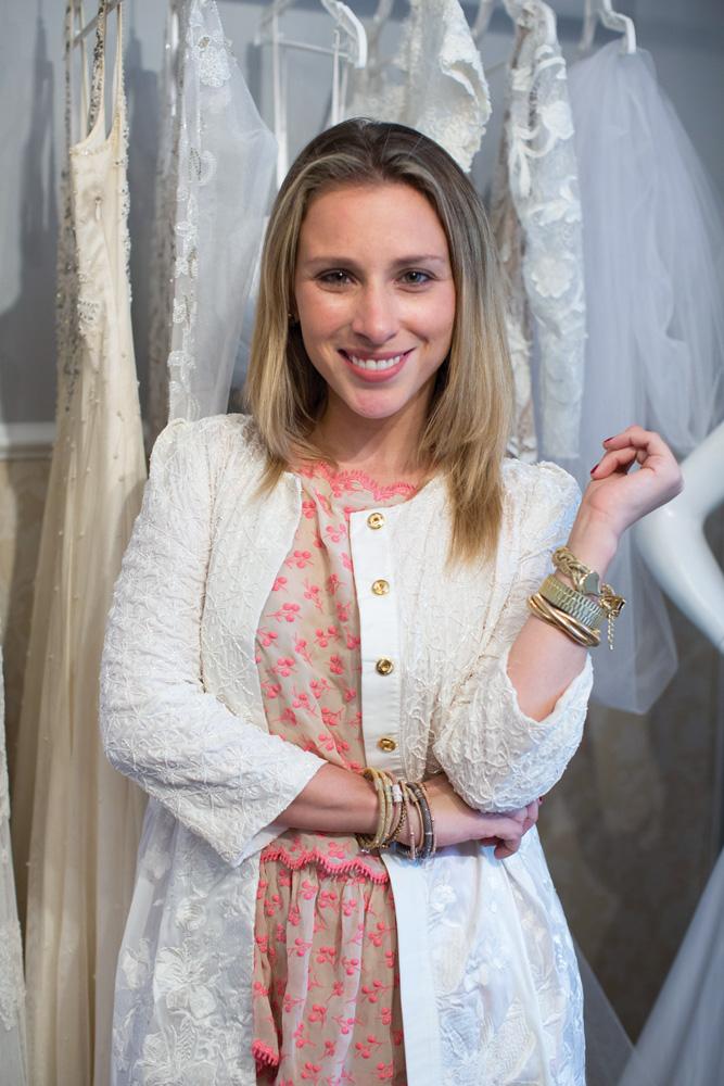 estilista Lethicia Bronstein sorrindo com um dos braços apoiando o outro, que está com a mão para cima e relaxada. ela está com uma blusa rosa por baixo de outra blusa, branca