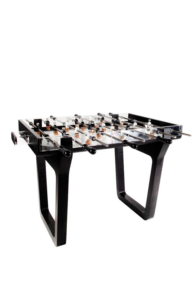 mesa de pebolim versão deluxe, construída com acrílico, metal e vidro, com fundo branco