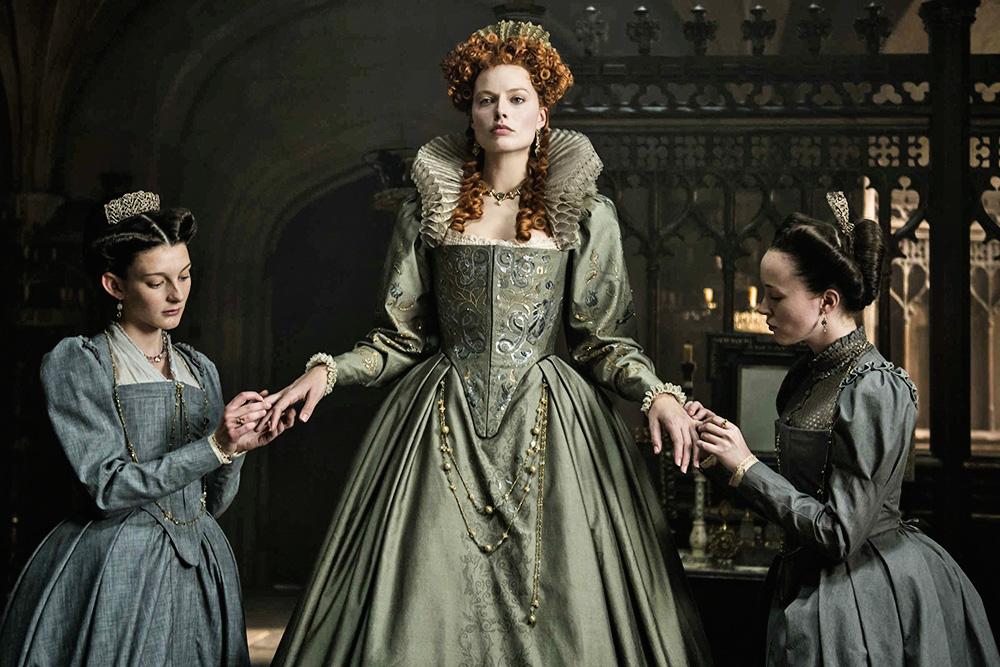 A imagem mostra Margot Robbie trajada de rainha, com duas súditas cuidando de suas mãos e ela de pé.