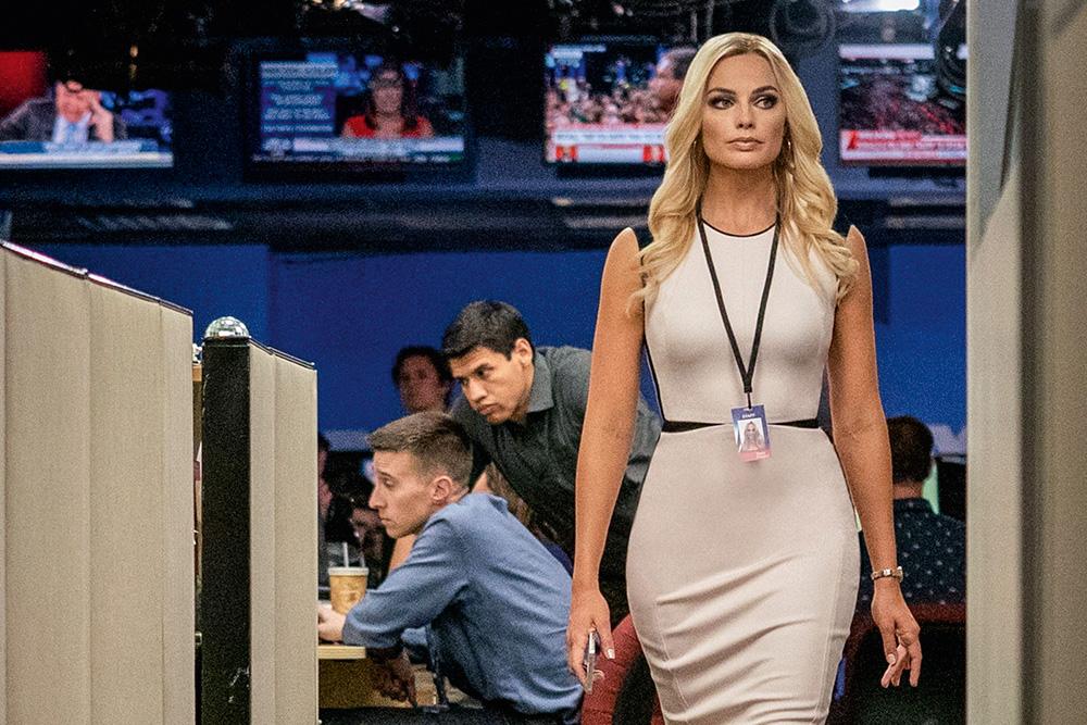 A imagem mostra Margot Robbie em uma redação televisiva enquanto caminha por ela, com um crachá.