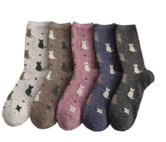 Cinco meias uma ao lado da outra. Nas cores branca, marrom, rosa, azul e preta, respectivamente. Elas têm desenhos de gatinhos em detalhe