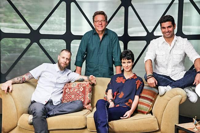 Jurados do The Taste Brasil nas gravações. Helena Rizzo e André Mifano sentados em sofá bege e Claude Troisgros e Felipe Bronze em pé atrás.