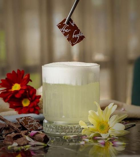 Drinque claro com espuma branca recebendo pedaço de chocolate com pinça escrito Beefbar.