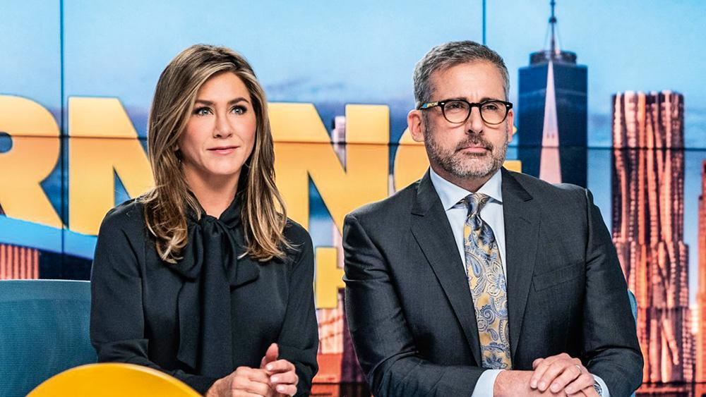 A imagem mostra Jennefir Aniston e Steve Carell em uma bancada de jornal televisivo, olhando para frente, durante a série The Morning Show