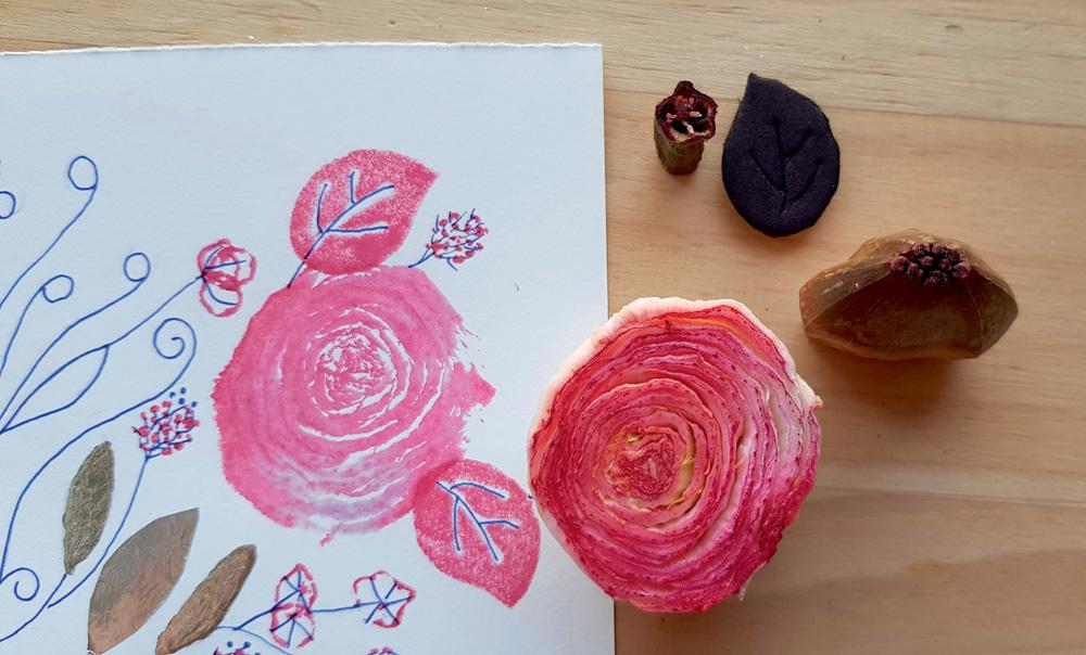 Uma folha de papel tem desenhos de folhas e rosas. Uma rosa real está do lado da folha
