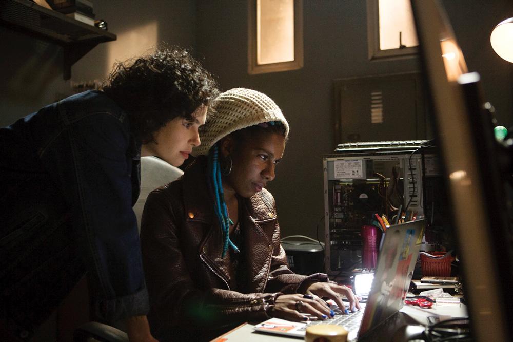 A imagem mostra duas mulheres em um quarto, pesquisando algo em um notebook que está de costas para a câmera. Cena da série Os Ausentes.