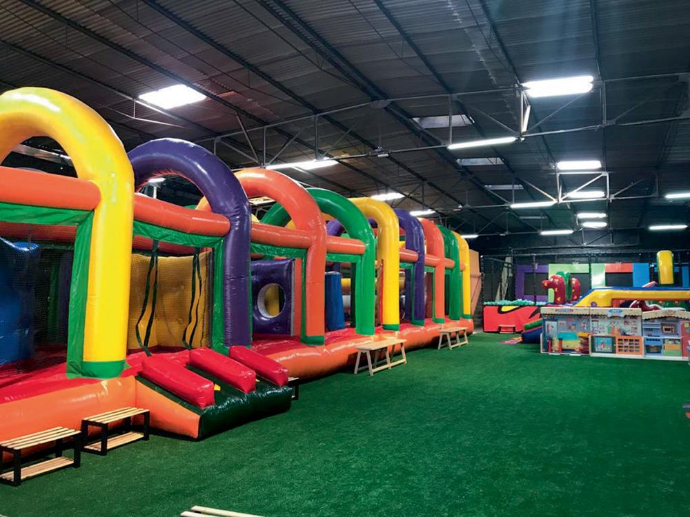 Um brinquedão de infláveis e obstáculos coloridos dentro de um grande salão