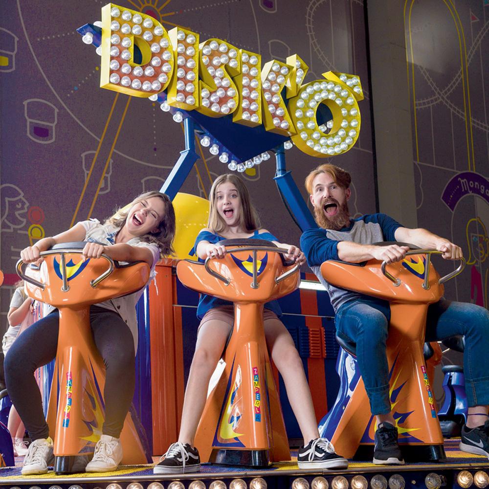 Três pessoas sorriem enquanto estão no brinquedo giratório