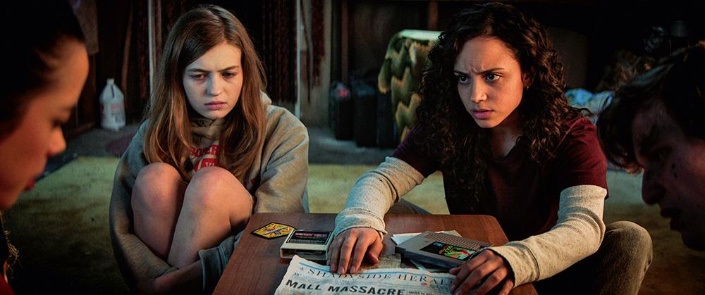 A imagem mostra três jovens, com caras sérias e preocupadas, olhando um para outro com uma mesa no centro entre eles.