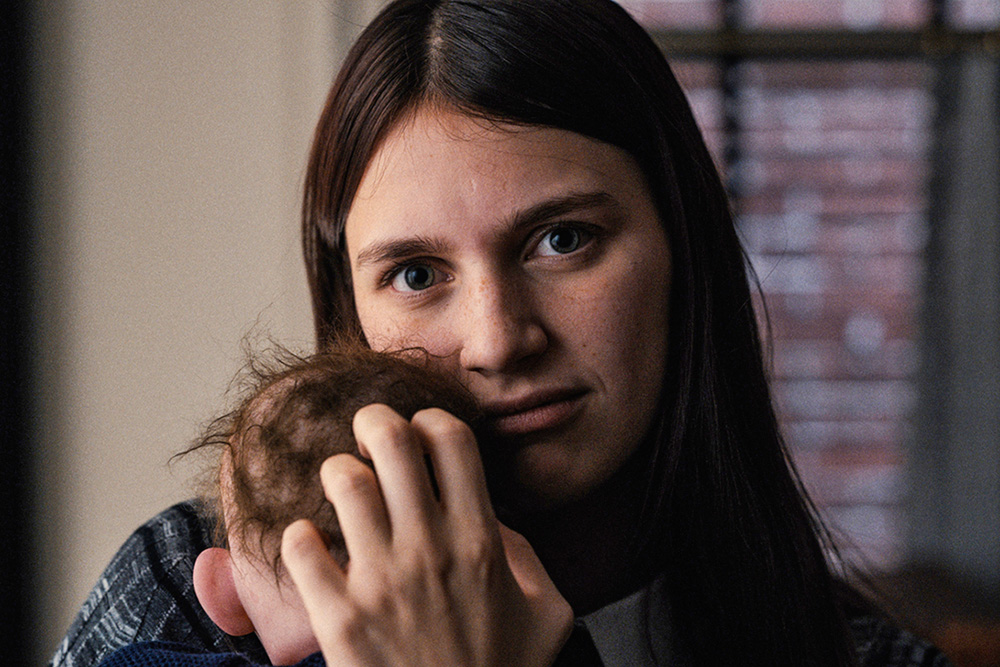A imagem mostra Lauren Ambrose segurando um bebê no coloco, fazendo cafuné em sua cabeça, que está de costas para foto. Ela, de frente, olha para a câmera com os olhos bem abertos.