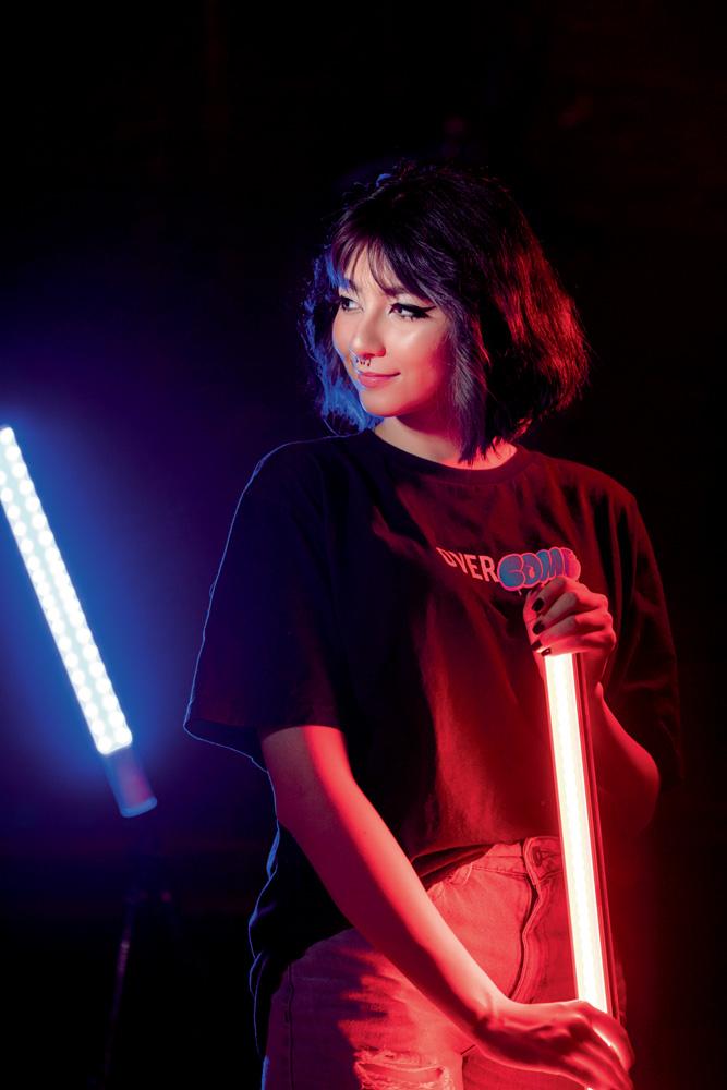 A imagem mostra Taynah, em um estúdio escuro, segurando uma barra de luz vermelha com outra barra azul ao fundo