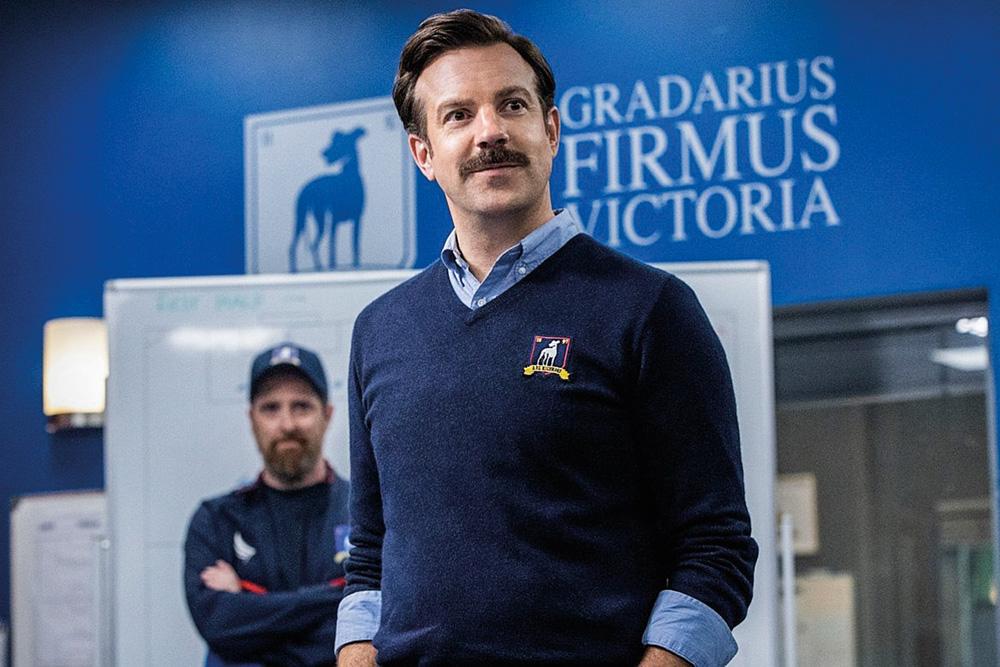 A imagem mostra o ator Jason Sudeikis, na série Ted Lasso, com um suéter com bordado do clube no qual é treinador e ele olhando para o vestiário onde está seu time