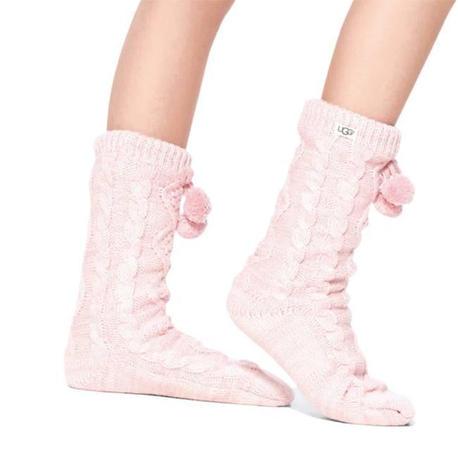 Um par de meias rosas claro com duas bolinhas de lã de enfeite