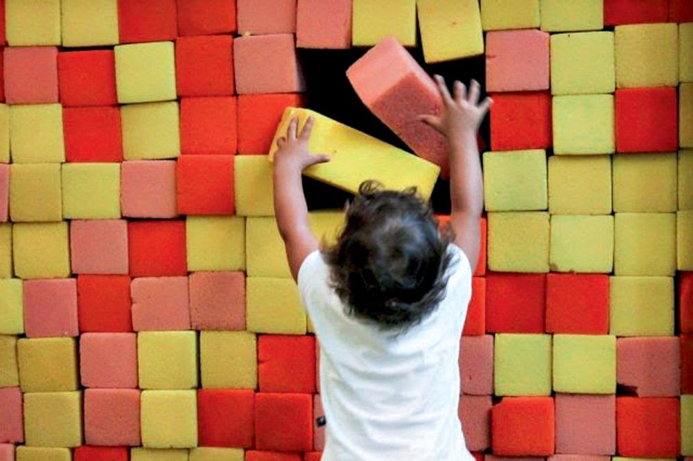 Criança monta uma parede de blocos amarelos, vermelhos e rosas