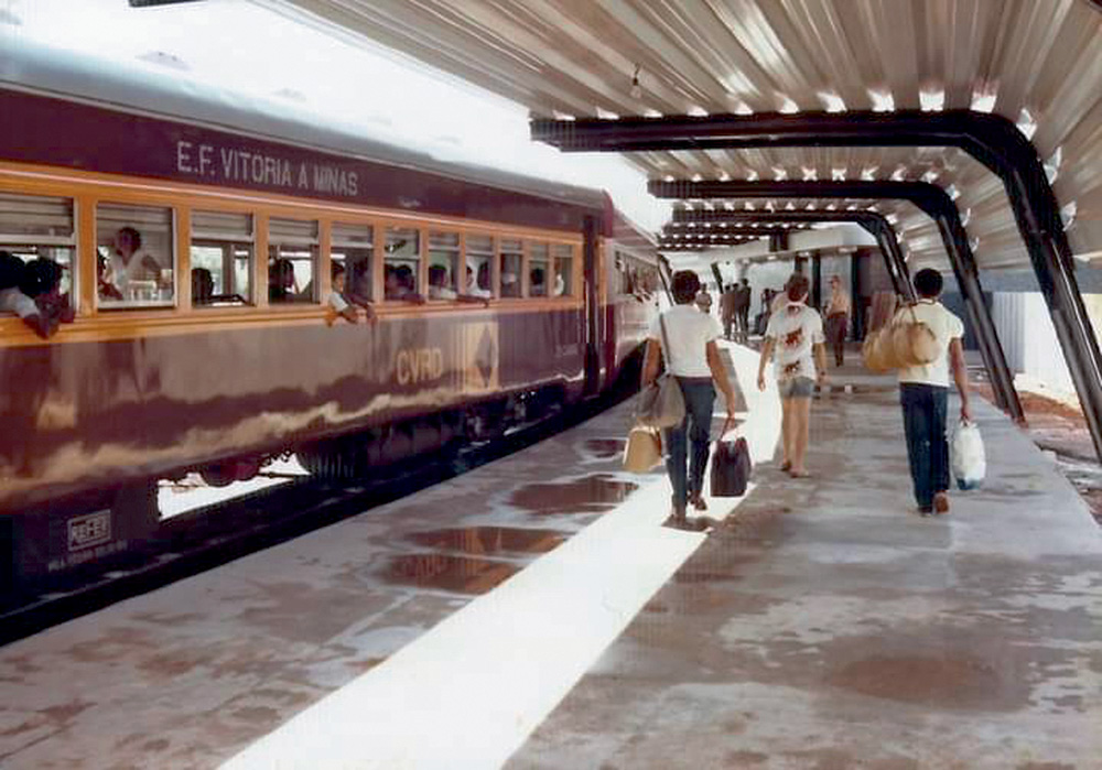Vagão que circulava de Vitória a Belo Horizonte aparece em foto de arquivo. Suas cores são amarelo e vinho. O vagão está parado e alguns passageiros circulam à direita na plataforma da estação.