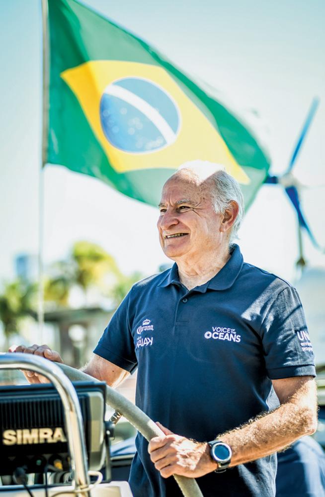 vilfredo sorrindo olhando para o horizonte segurando o voltante do barco Kat. ao fundo, tem uma bandeira do brasil balançando ao vento