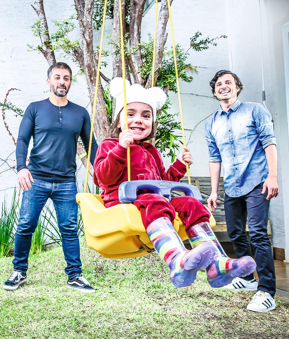 A imagem mostra Rogerio e Gustavo e a filha Alice em um balanço. Os três estão sorrindo.