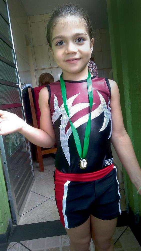 A imagem mostra Rafaelly, em pé, com uma medalha e seu uniforme de ginasta.