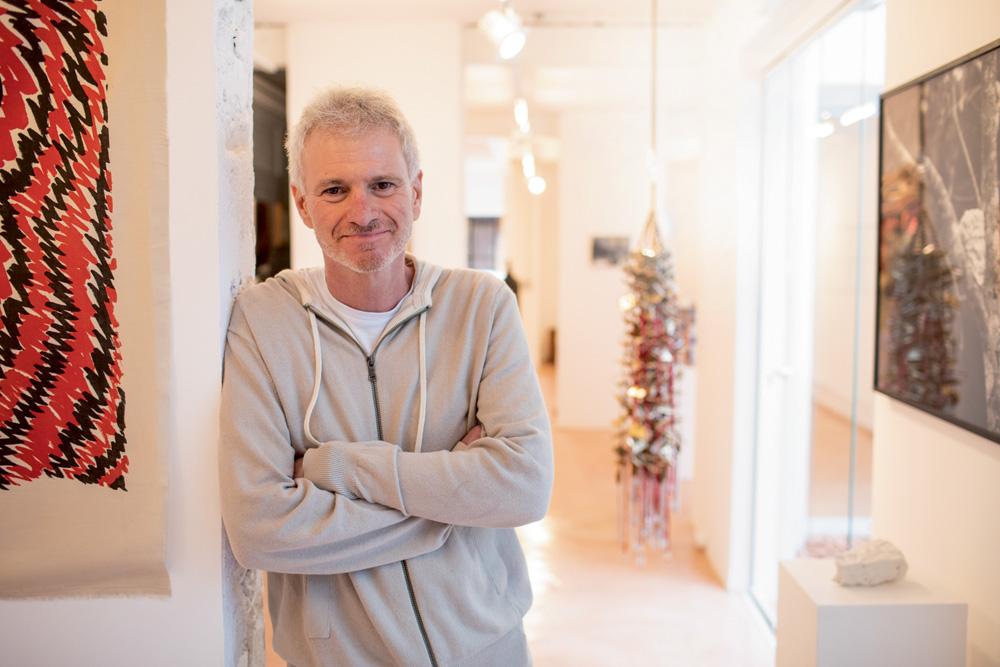 Homem grisalho se apoia em uma parede de uma galeria com os braços cruzados e sorri para a foto