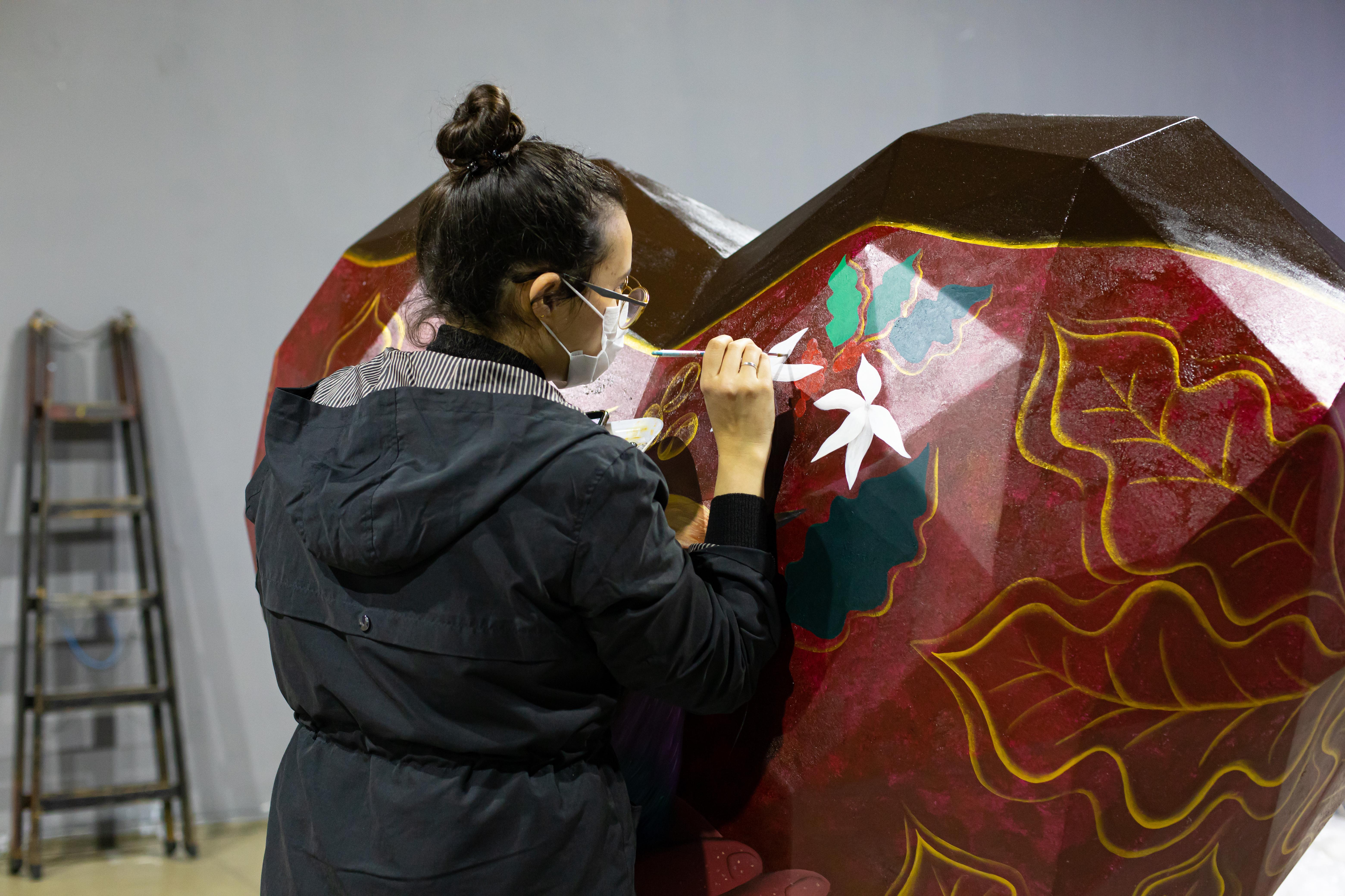 A imagem mostra um coração artístico, de mais de um metro de altura e largura. Ele está apoiado em uma estrutura de madeira e sendo pintado por outra pessoa.