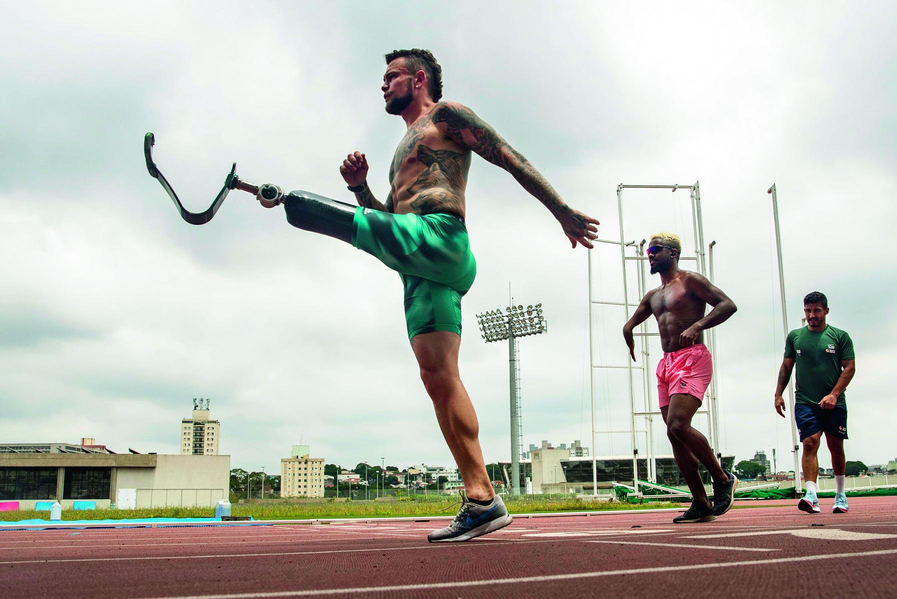 Atleta Vinícius Rodrigues, que tem uma perna amputada, levantando-a na pista de corrida. Há outros dois atletas atrás dele