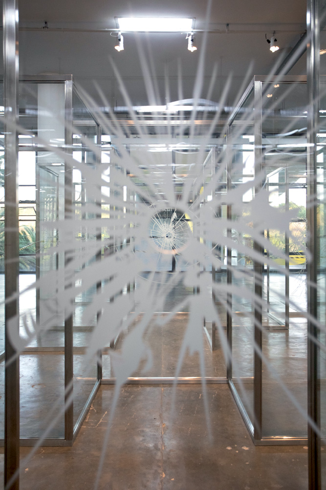 A imagem mostra um labirinto de placas de vidros. Nas telas, há danos semelhantes a de marcas de balas.