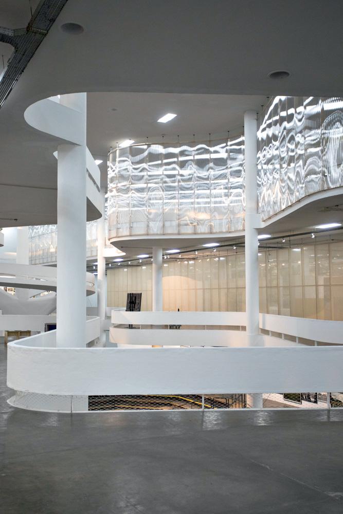 A imagem mostra artes interagindo com a estrutura da Bienal.