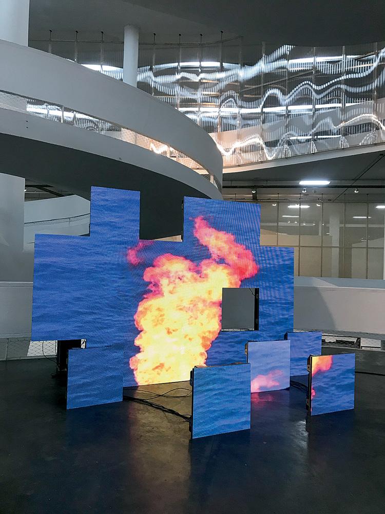 A imagem mostra um painel de telas de led. Cada uma delas compõe a imagem de chamas em fundo preto. Elas estão espalhadas em um plano, sem uniformidade.