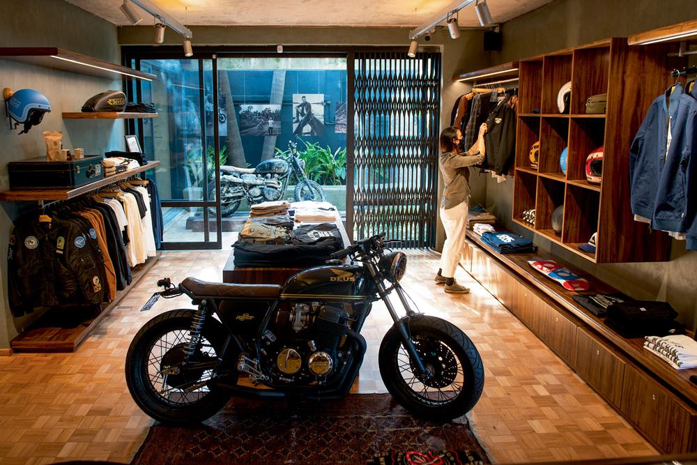 A imagem mostra a fachada da Deus Ex Machina. Nela, há roupas em exibição e uma moto no centro da loja.