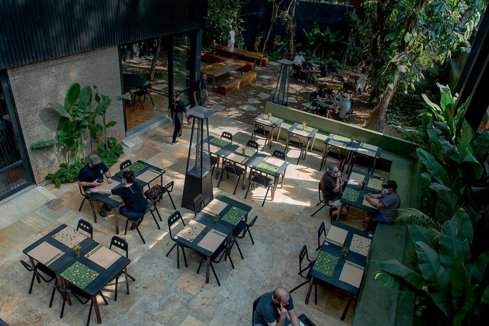 A imagem mostra o fundo da Deus Ex Machina. Lá, há mesas para quatro pessoas e uma área verde com algumas árvores.