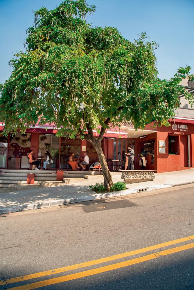 Fachada do Camélia Òdòdó, pintada em cor avermelhada. Na calçada, algumas mesas estão espalhadas. À frente, uma grande árvore faz sombra no ambiente