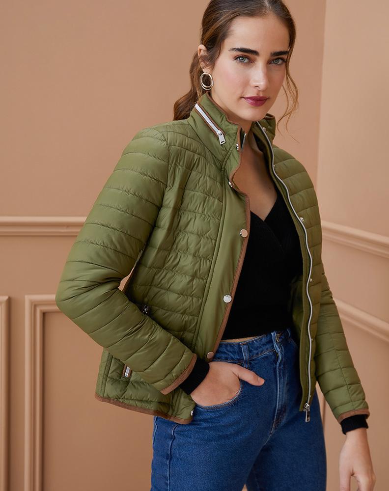 Mulher posa vestindo casaco puffer verde e com a mão no bolso da calça