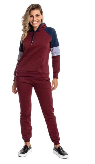 Mulher loira sorri para câmera vestindo conjunto de calça e moletom na cor vinho que combinam