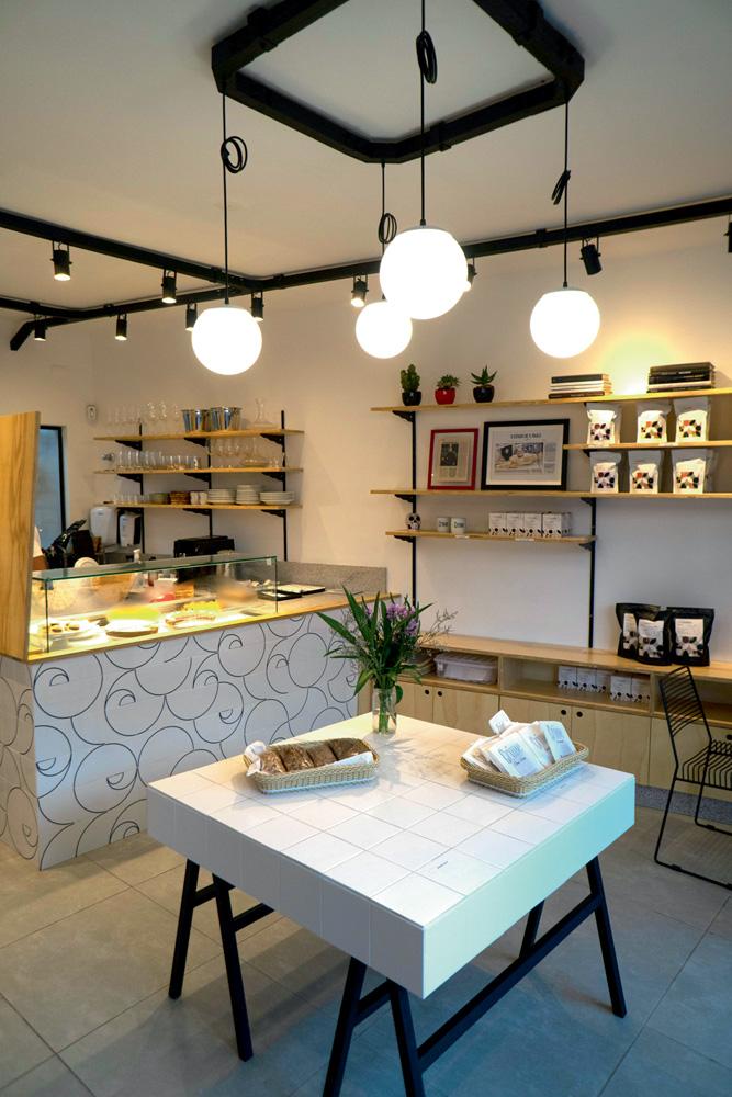 Salão da Crime Pastry SHop, com vitrine de doces à esquerda, mesa branca quadrada ao centro e prateleiras de madeira no fundo à direita.