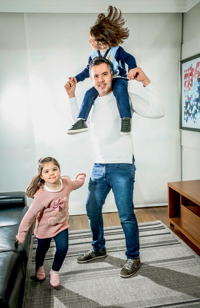 A imagem mostra Eduardo, sorrindo, com Vitor sobre seus ombros, de cavalinho, e Julia correndo em volta dos dois em uma sala.