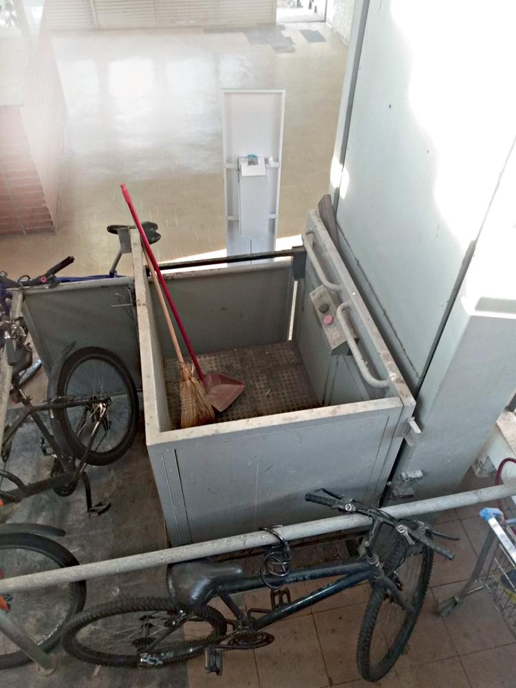 Um elevador visto de cima. Há bicicletas ao lado da estrutura, que está aberta com uma vassoura dentro