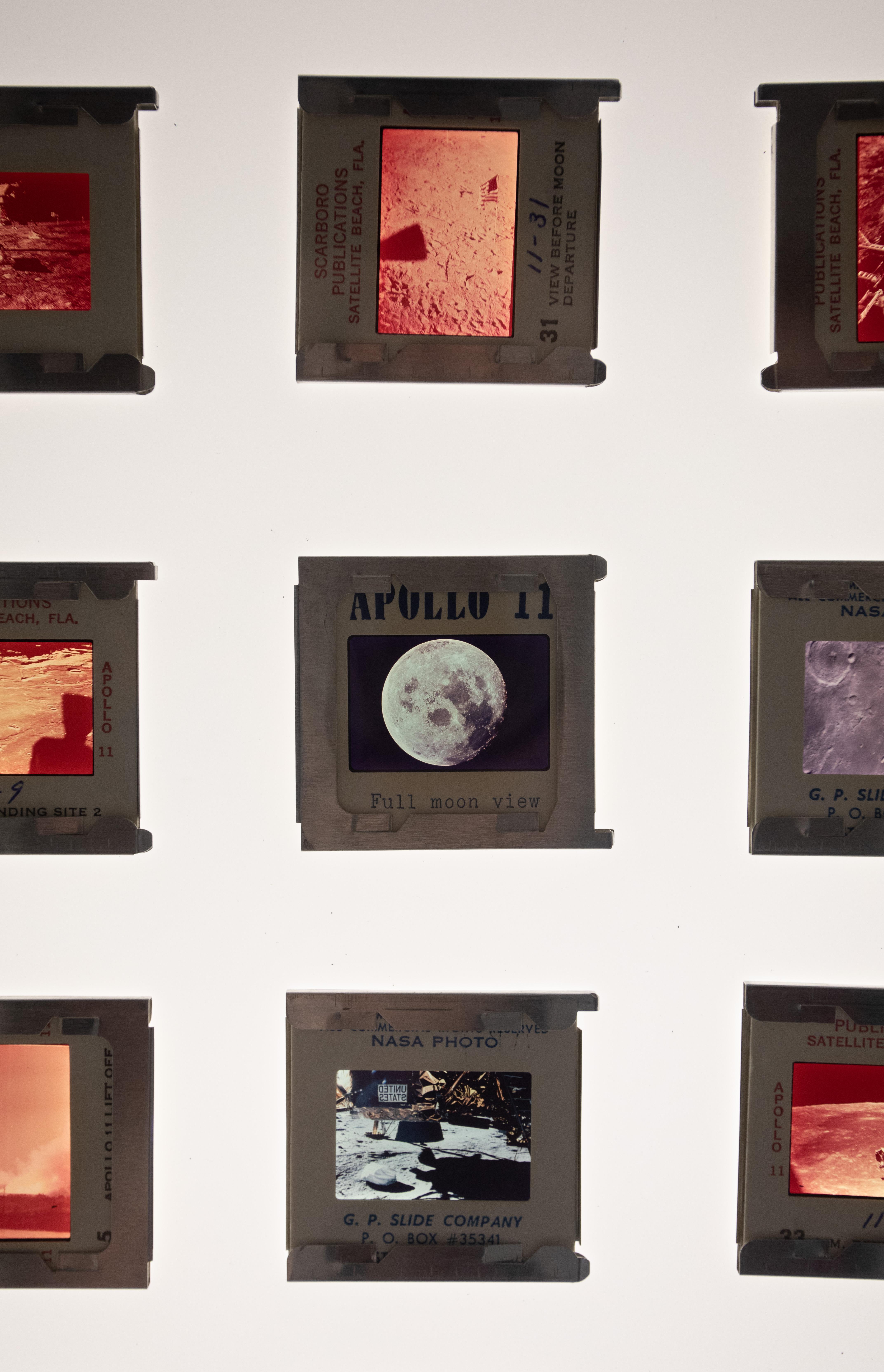 Fotos de missões espaciais aparecem alinhadas na parede.