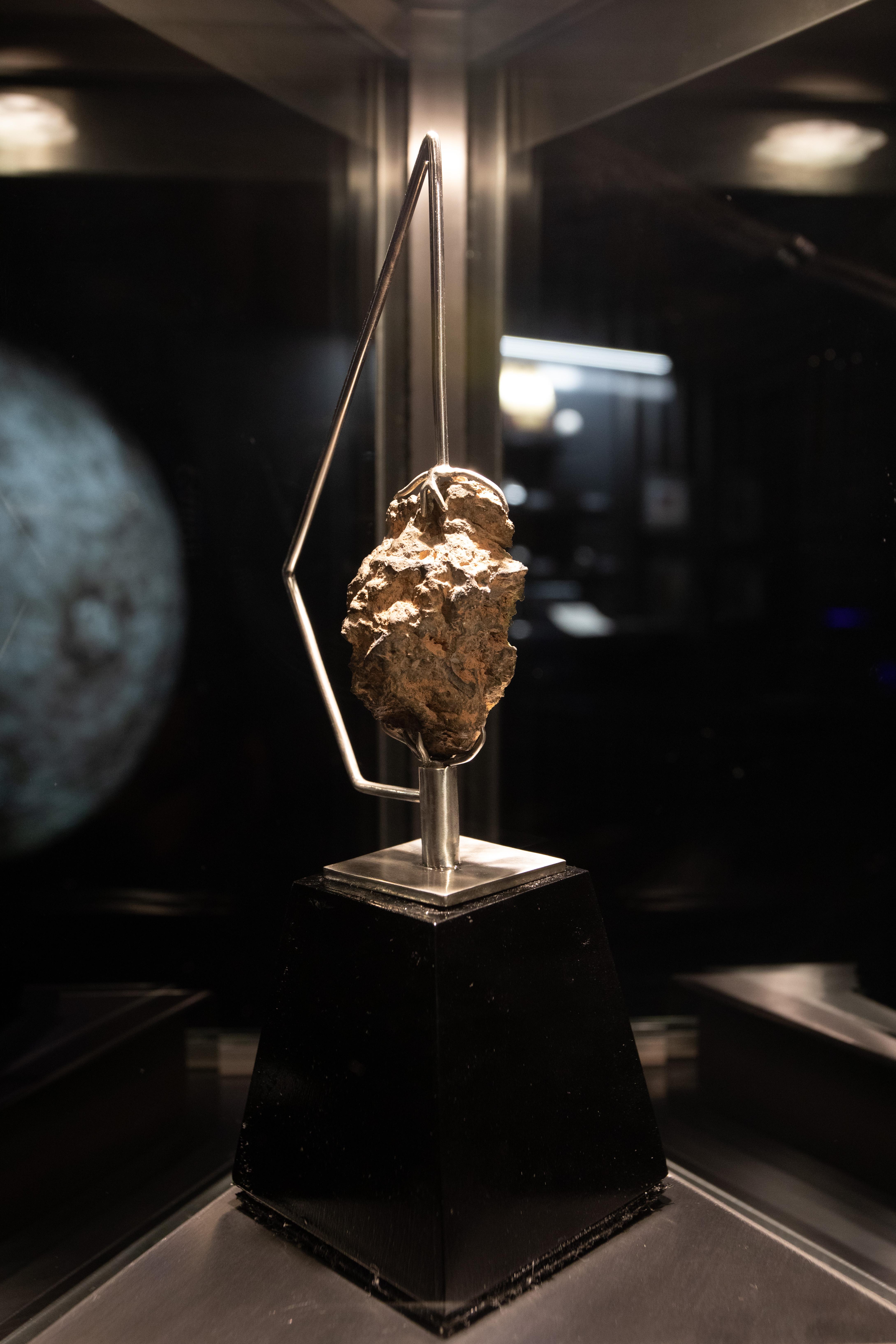 Rocha lunar é exibida em iluminação especial com foto da Lua ao fundo.