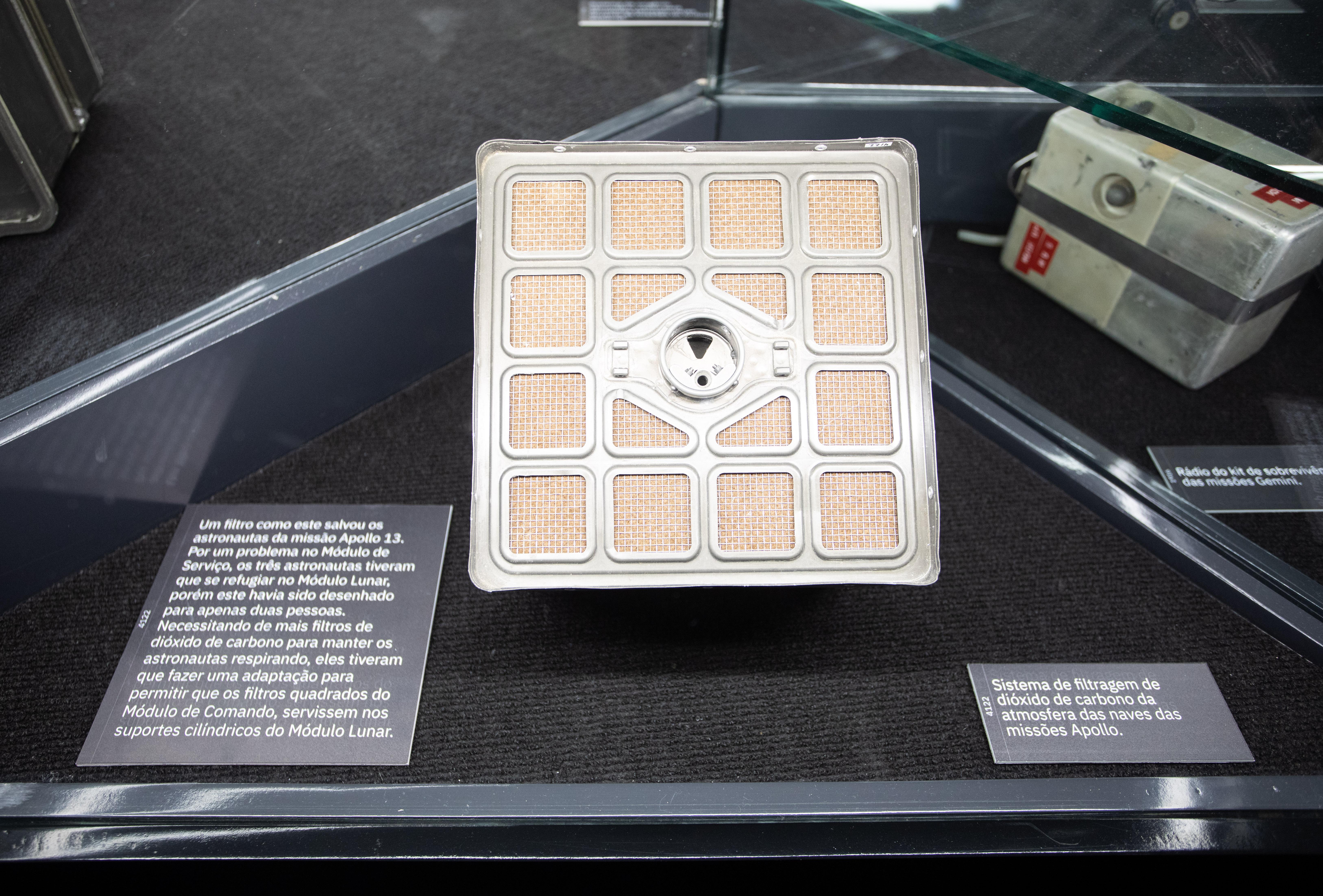 Filtro que que salvou a vida de tripulantes da Apollo 13 aparece dentro de vidro com quadradinhos amarelados em um quadrado de prata.