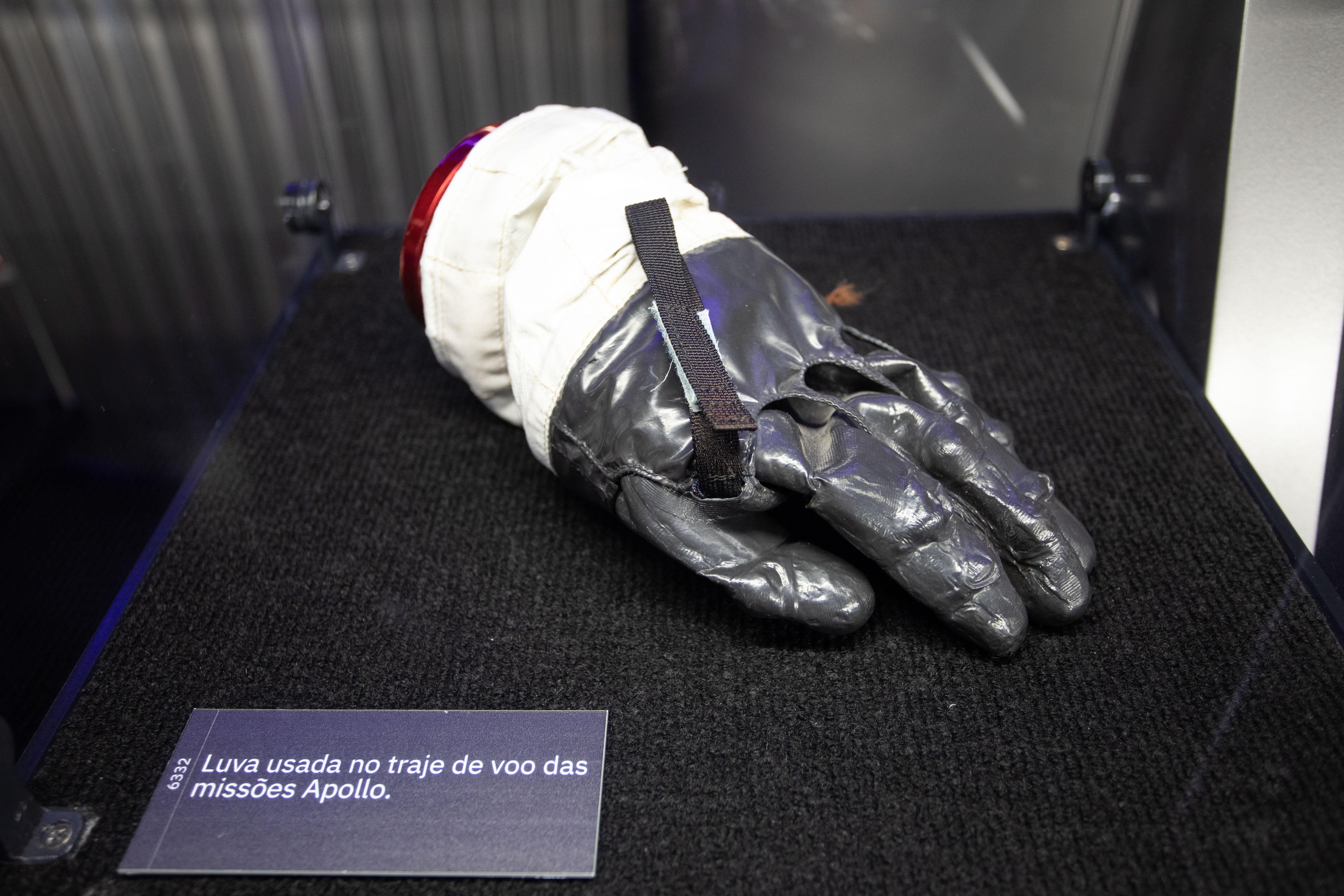 Luva usada nos trajes de voo das missões Apollo aparece dentro de vidro.
