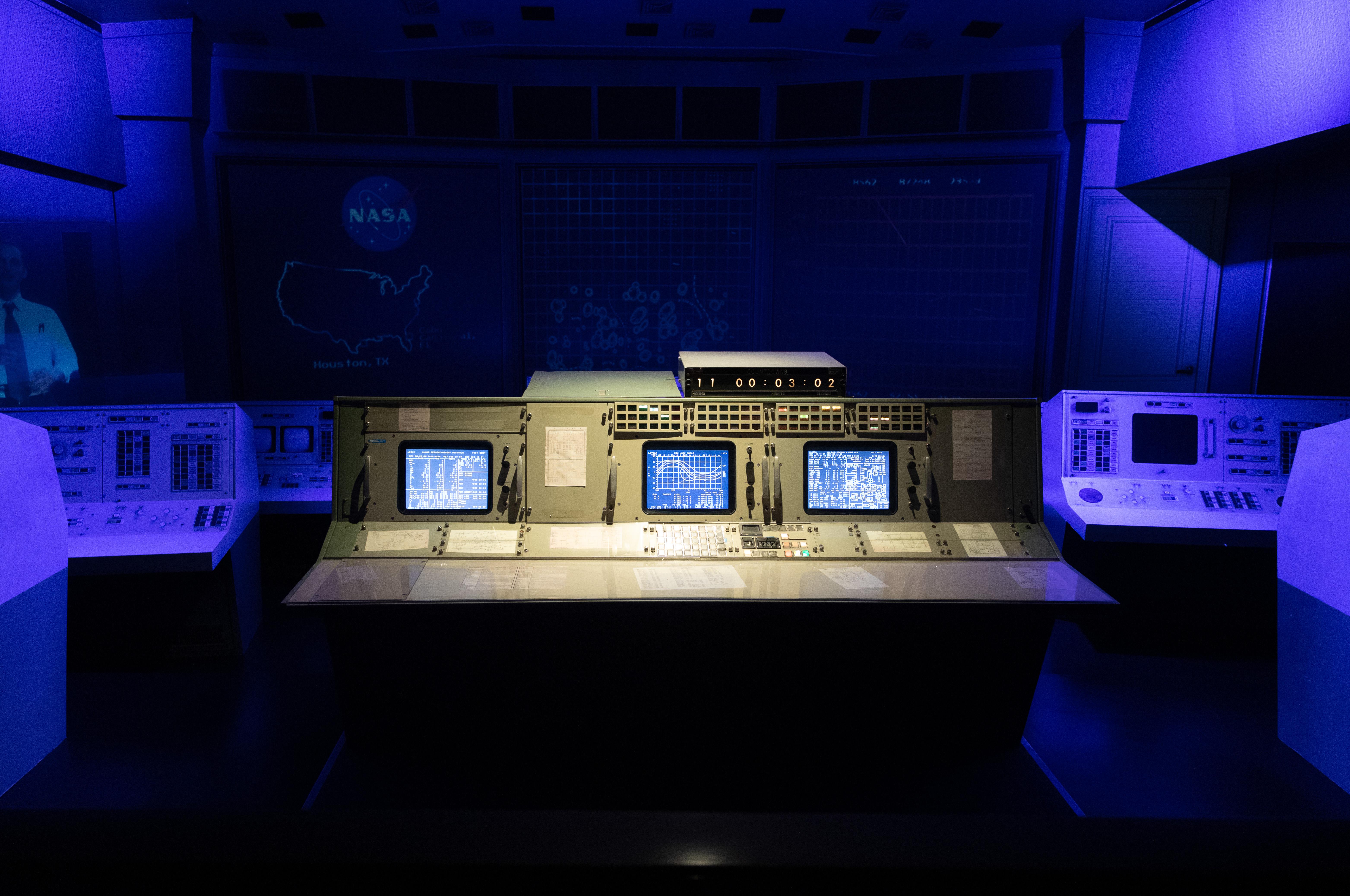 Painel de controle de missão espacial aparece iluminado em local escuro e azulado.