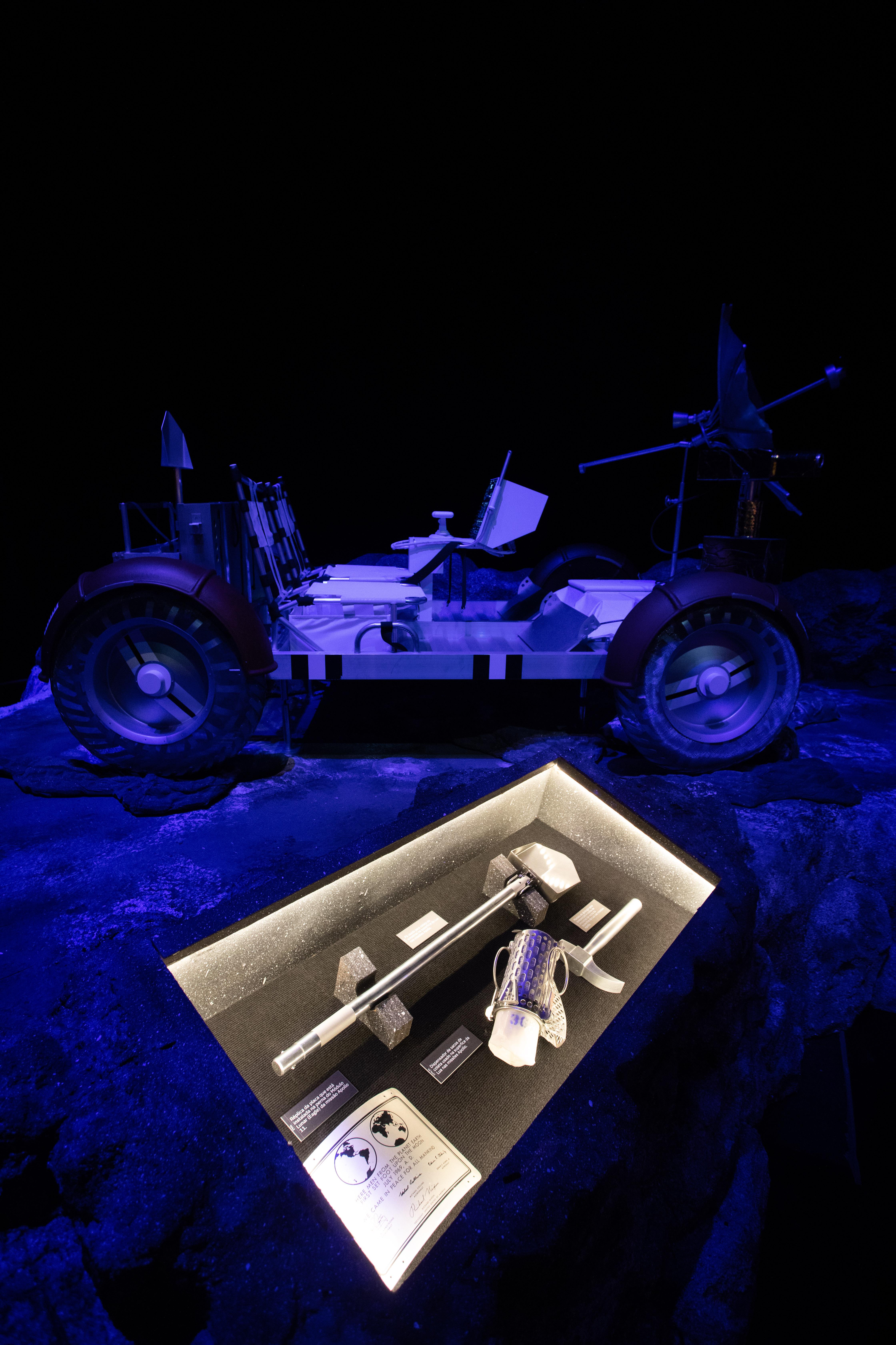 Foto mostra carro lunar e martelo prata.