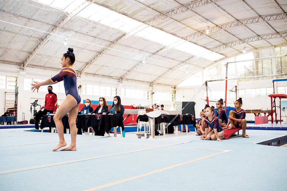 A imagem mostra o centro de ginástica de São Bernardo. Crianças estão observado uma ginasta preparando para fazer um movimento