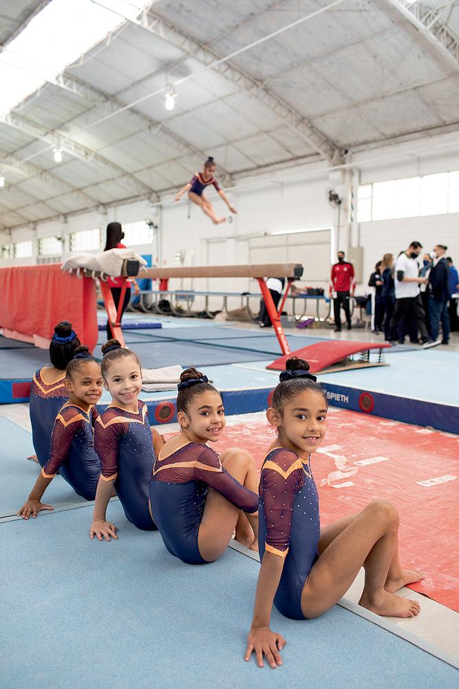 A imagem mostra cinco ginastas jovens sentadas a beira de um chão para a prática da ginástica.