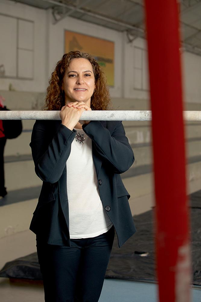 A imagem mostra Mônica, de pé, com as duas mãos apoiadas sobre uma barra de ginástica. Ela olha para a câmera sorrindo.