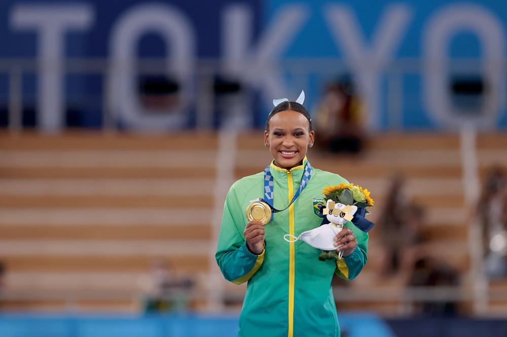 A imagem mostra Rebeca segurando a medalha de ouro no pódio